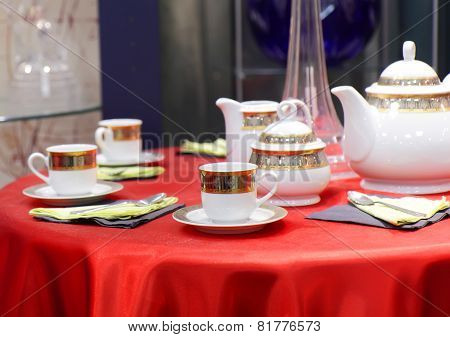 Table Appointments On Red Tablecloth.