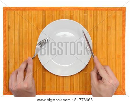 Hands Hold Fork And Knife Above Plate.
