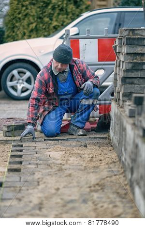 Concentrated Workman Laying Paving Bricks In Winter