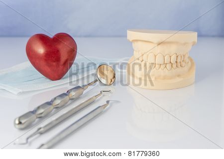 Dental mold with tools of a face mask and red heart.