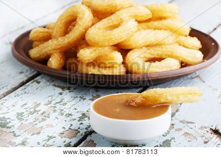 churros sweet dessert with caramel plate on a wooden surface