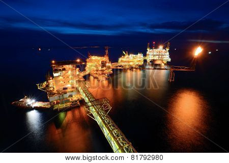 The supply boat is working at large offshore oil rig at night with twilight background