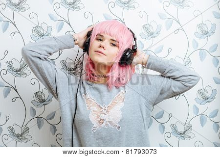 Young hipster woman in pink wig and dj headphones enjoying music indoor