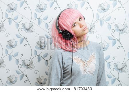 Young hipster woman in pink wig and dj headphones enjoying music