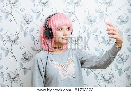 Young hipster woman in pink wig and dj headphones doing selfie