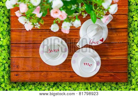 Top View Of The Teapot, Empty  Teacup And Artificial Flowers On A Wooden And Green Clover