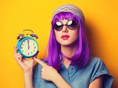foto of violets  - Beautiful girl with violet hair in sunglasses and alarm clock on yellow background - JPG
