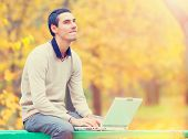 image of programmers  - Programmer with notebook sitting in autumn park - JPG