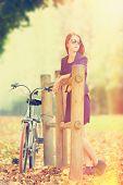 stock photo of versaille  - Beautiful redhead women with bike in Versailles gardens - JPG