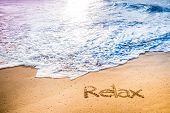 picture of relaxing  - The word RELAX written into the sand on a tropical sandy beach in paradise - JPG