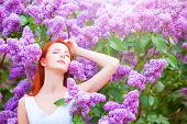 image of redhead  - Redhead girl near lilac tree in the garden - JPG