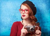 foto of beret  - Redhead women in beret with camera on blue background - JPG