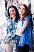 stock photo of graffiti  - Two beautiful girls near a graffiti wall - JPG