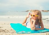 pic of sunbather  - Little girl sunbathing on the beach - JPG