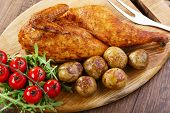 picture of baked potato  - half baked chicken with new potatoes on the board - JPG