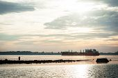 pic of barge  - silhouette of a fisherman and a barge on the river - JPG