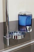 stock photo of dispenser  - Faucet with soap dispenser in clean  bathroom - JPG