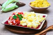 stock photo of cassava  - Cooked cassava or manioc with a cooked vegetable mix of onion Peruvian or Cuzco corn and tomato photographed with natural light  - JPG