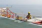 picture of helicopters  - fireman is guarding for offshore helicopter before start up engine at oil rig platform - JPG