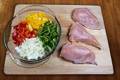 stock photo of enchiladas  - Fresh enchilada ingredients on chopping block including fresh chicken and peppers - JPG