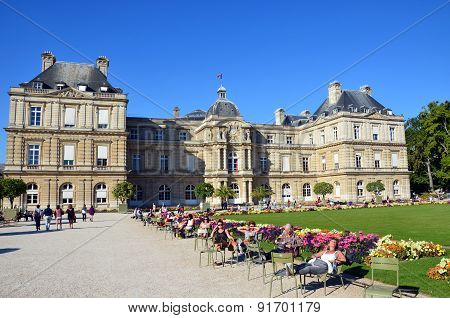 People enjoy sunny day in the Luxembourg Garden in Paris