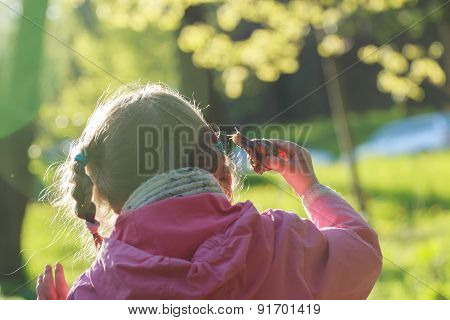 Back View Of Preschooler Girl Holding Edible Snail In Her Arm