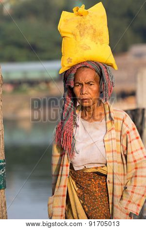 AMARAPURA, MYANMAR, JANUARY 18, 2015: A woman is carrying a bag on her head, walking on the U-bein bridge in Amarapura, Myanmar (Burma).