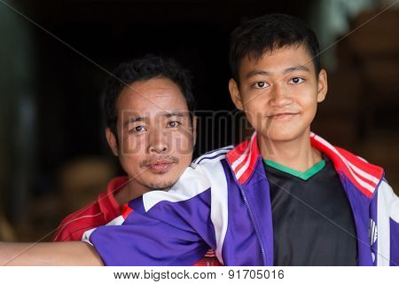MANDALAY,MYANMAR,JANUARY 17, 2015: Father and son sellers are posing in the central street market of Zegyo, in Mandalay, Myanmar (Burma).