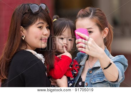 MANDALAY,MYANMAR,JANUARY 16, 2015: Korean women are shooting a selfie (self portrait) with a funny bored little girl in a street of Mandalay, Myanmar (Burma).
