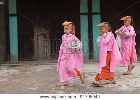 MANDALAY,MYANMAR,JANUARY 17, 2015: A group of young Buddhist nuns is walking in the streets of Mandalay, Myanmar (Burma).