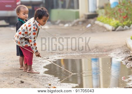 MANDALAY,MYANMAR,JANUARY 19, 2015: Kids playing with a stick in a puddle near the river Irrawaddy banks in Mandalay, Myanmar (Burma).