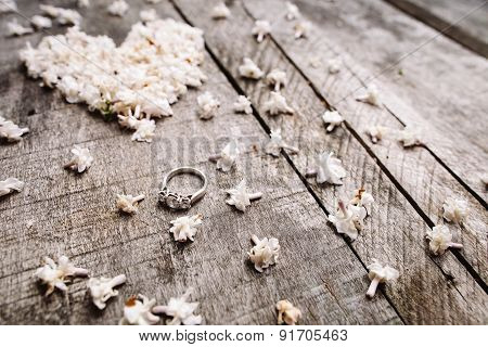 Gentle White Heart Shape Flowers With Ring On Wood Table
