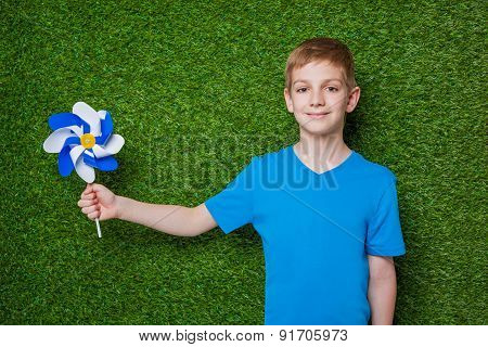 Boy holding pinwheel over green grass