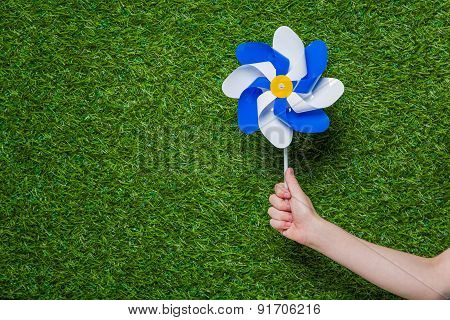 Hand holding pinwheel over green grass