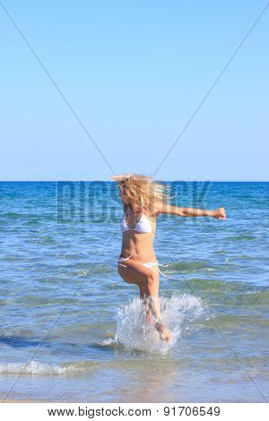 Young blonde woman having fun in the sea - Motion blur