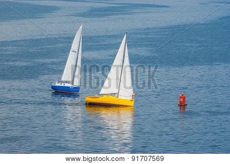 Two yachts turning of the sailing race on the Dnepr river
