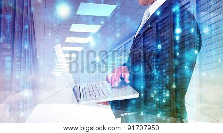 Businessman holding laptop against server hallway