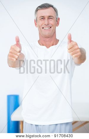 Happy patient looking at camera thumbs up in medical office