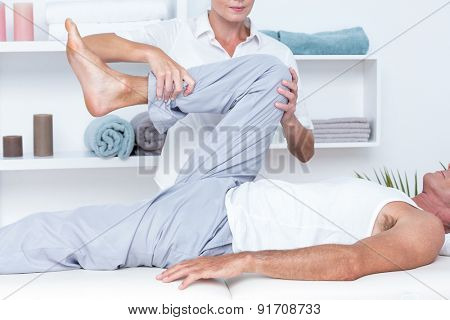 Physiotherapist doing leg massage to her patient in medical office