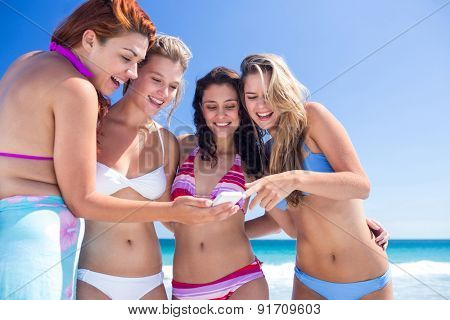 Happy friends looking at smartphone at the beach
