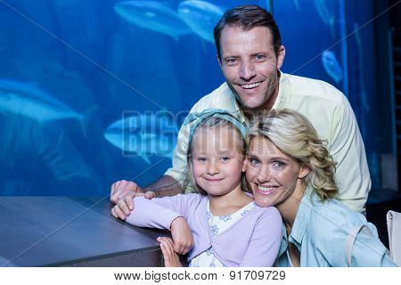 Happy family looking at camera beside the fish tank at the aquarium