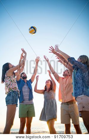 Happy friends throwing volleyball at the beach