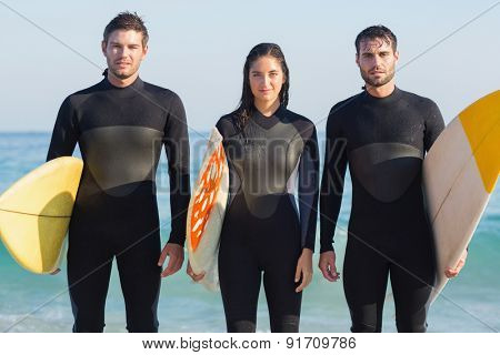 Group of friends in wetsuits with a surfboard on a sunny day at the beach