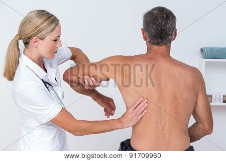 Doctor examining her patient arm in medical office