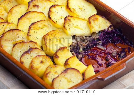 potatoes baked with pork minced meat and red cabbage