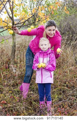 Mother and her daughter with autumnal apple tree holding an apples
