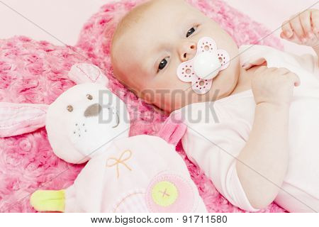 portrait of three months old baby girl with a toy