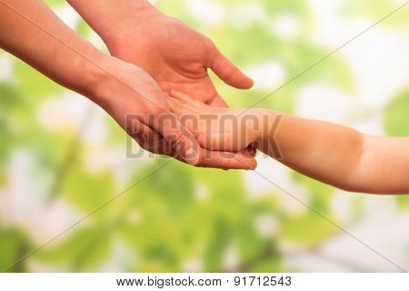 Male hand holding child