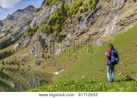 Woman Tourist With Backpack Hiking On Alps