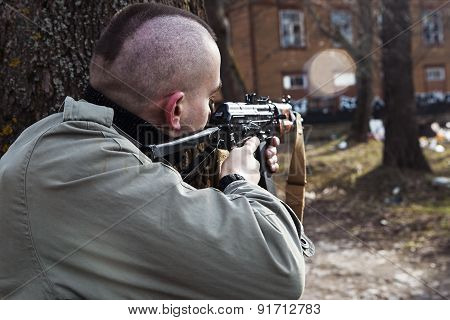 A Skinhead Male With The Gun Is Threatening To Someone Behind The Trees